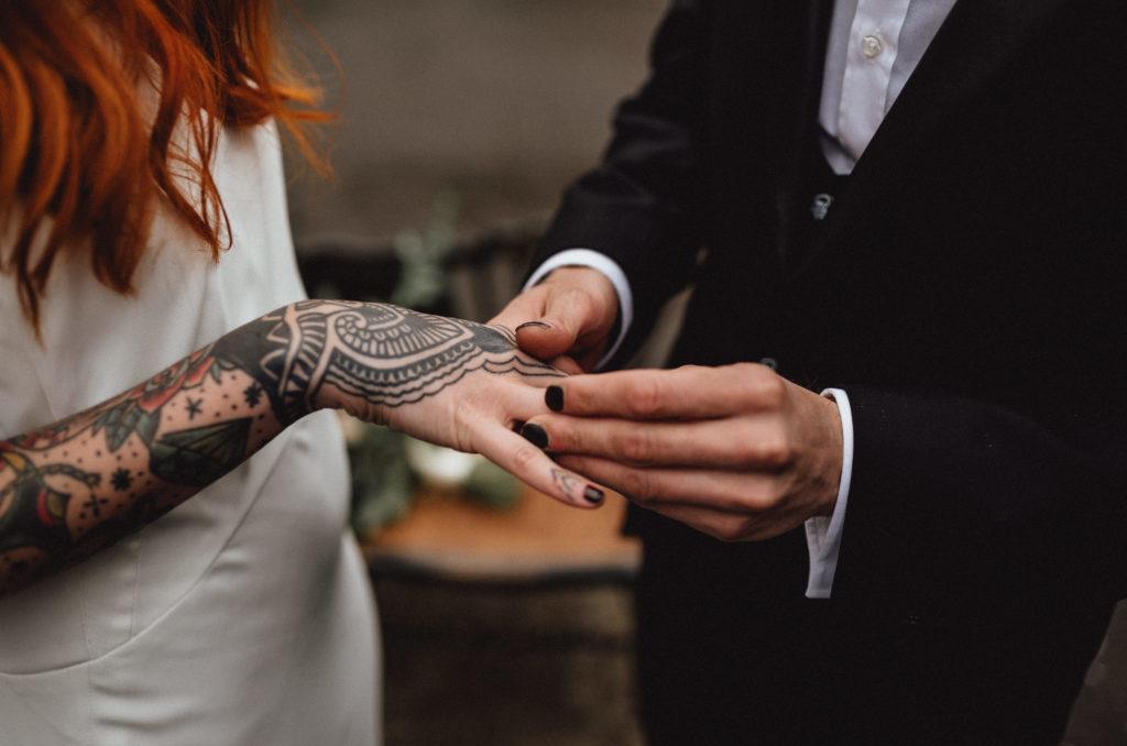 El novio le pone el anillo a la novia en una boda muy rock-era