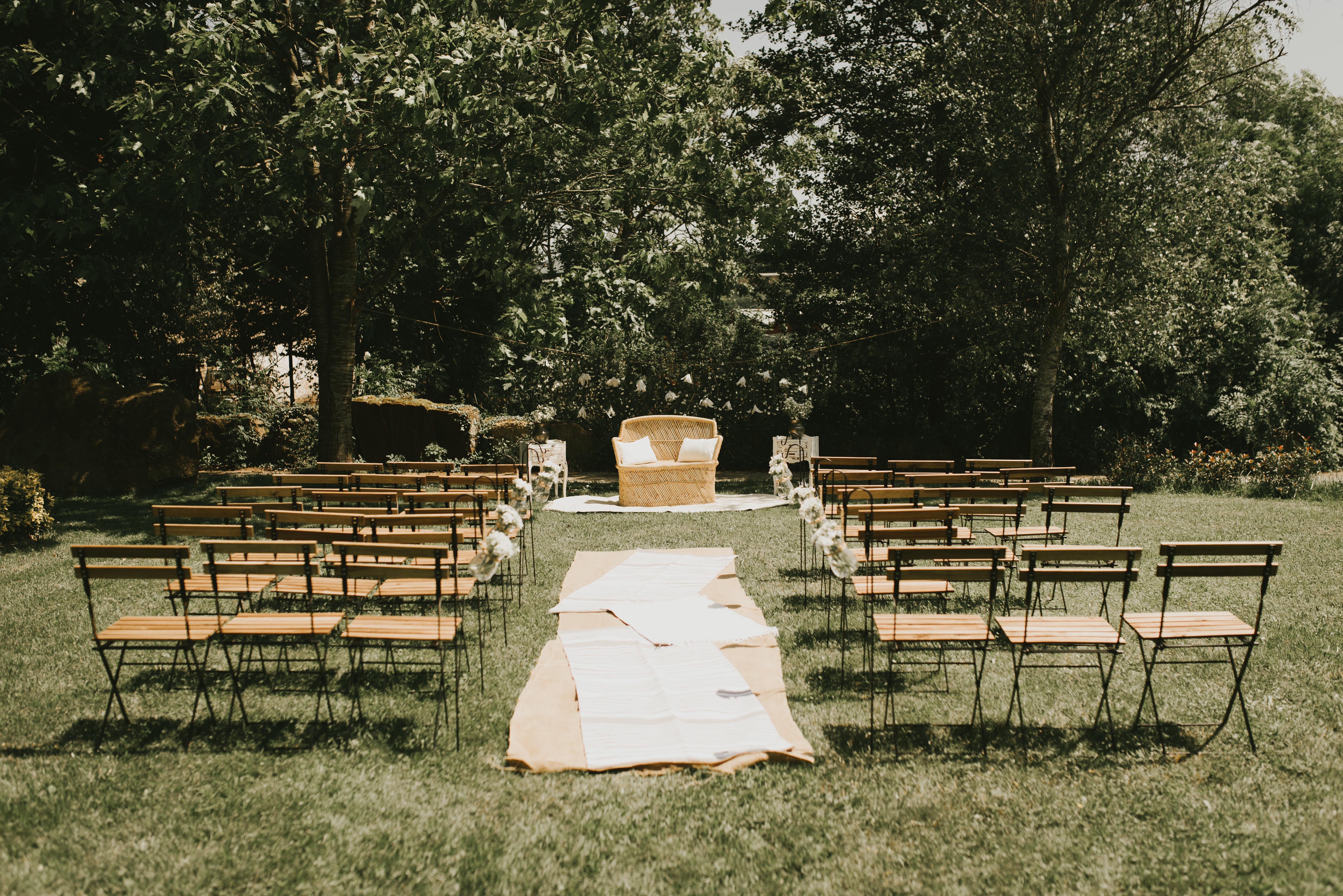 Ceremonia nupcial con sillón doble ratán, alfombras y sillas de forja y madera en entorno natural