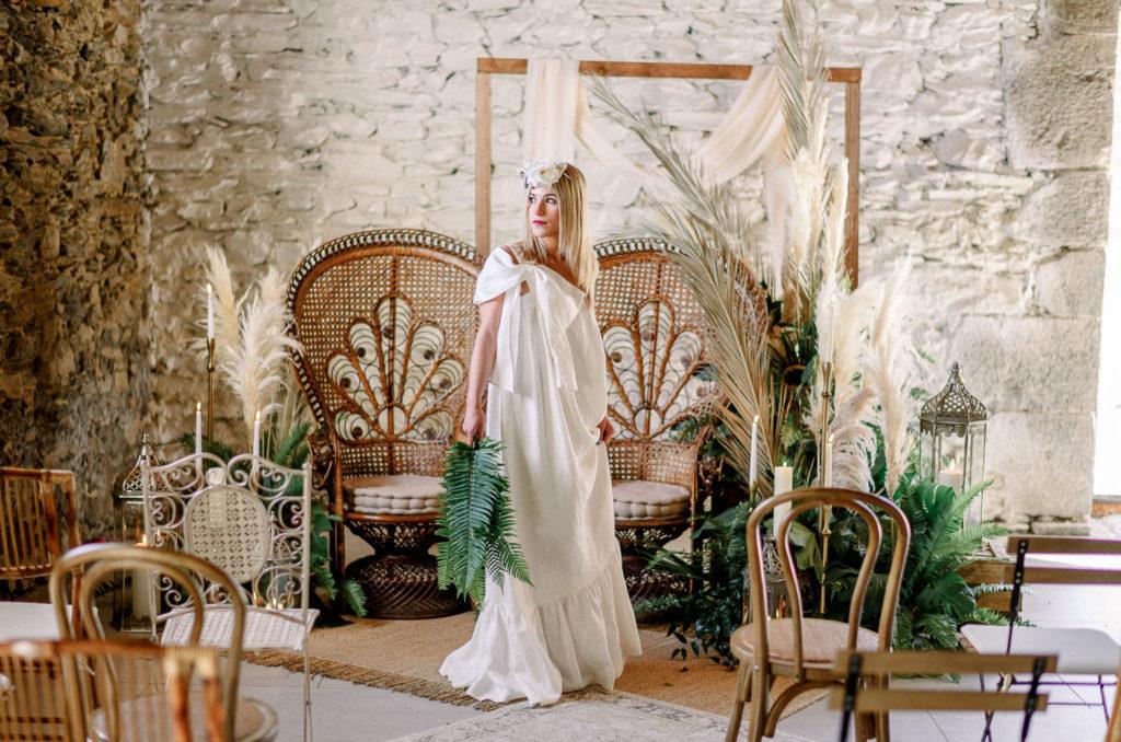 Novia posando en la ceremonia frente a sillones y arco nupcial