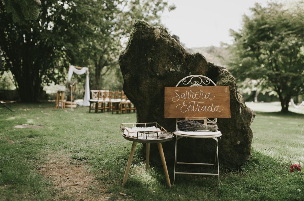 Rincón de bienvenida nupcial, sillas de forja blanca con cartel de entrada y mesa auxiliar
