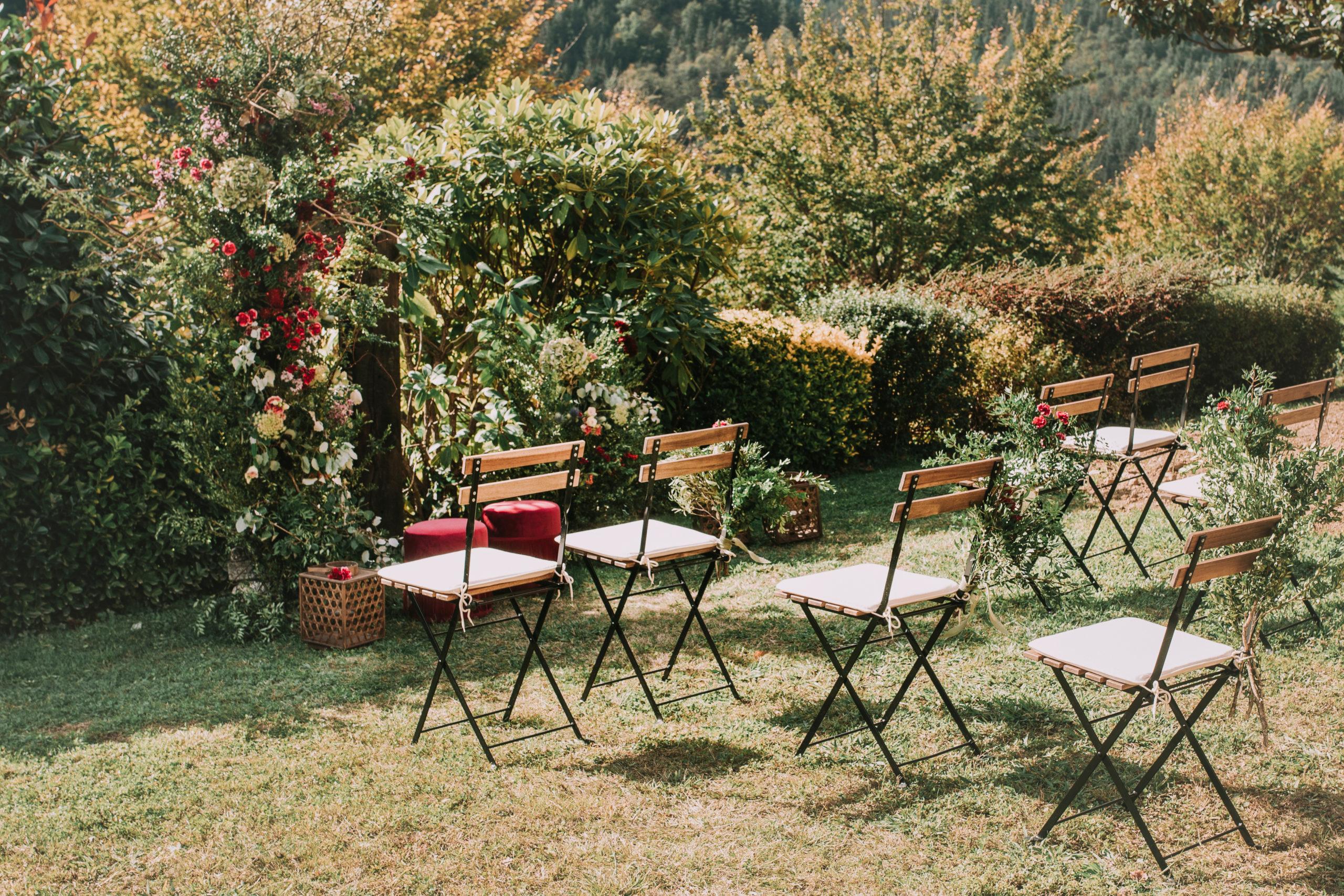 Ceremonia natural con sillas de forja y madera para los invitados