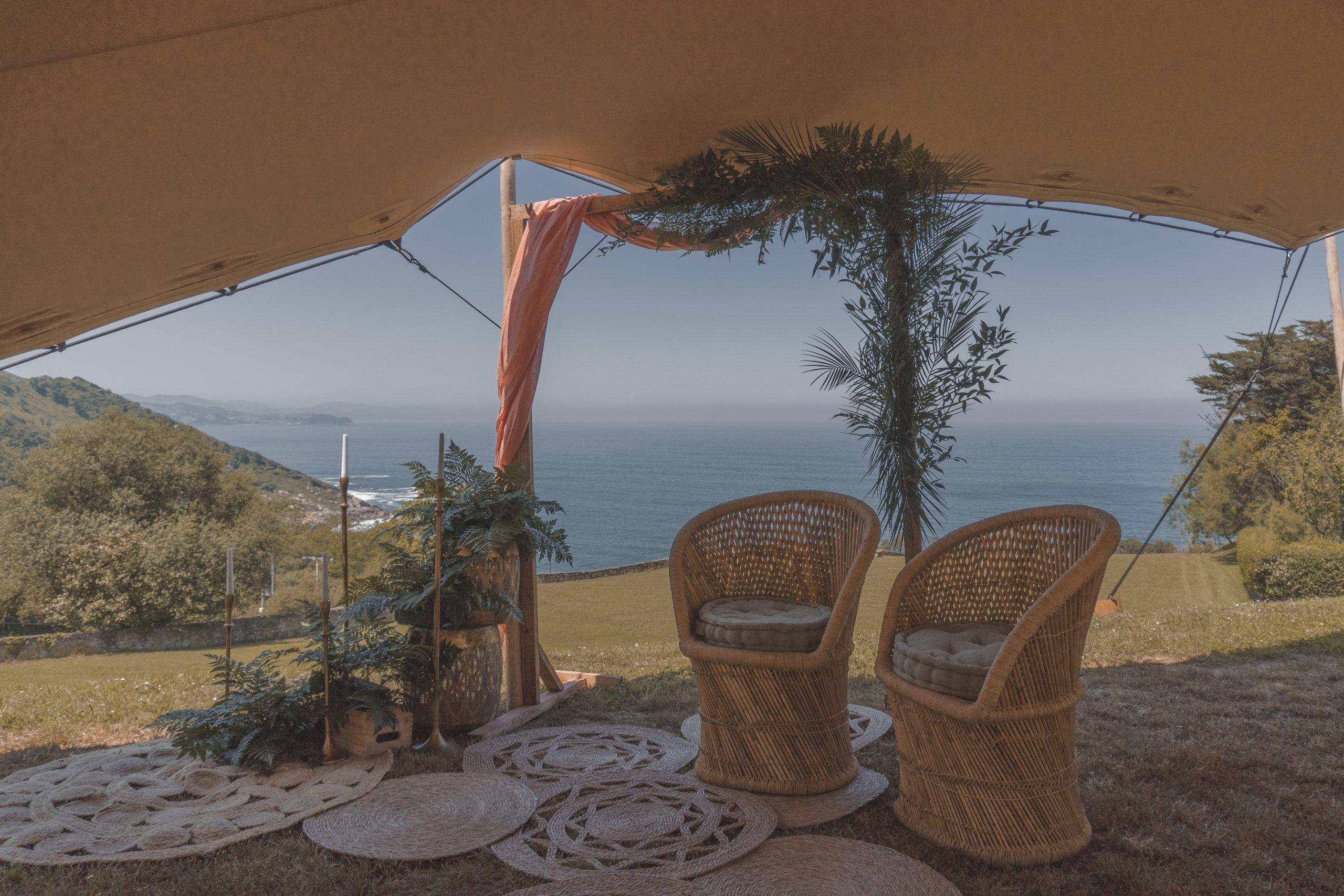 Ceremonia bajo una carpa: con sillones ratán individuales, arco, alfombras varias y decoración floral frente al mar