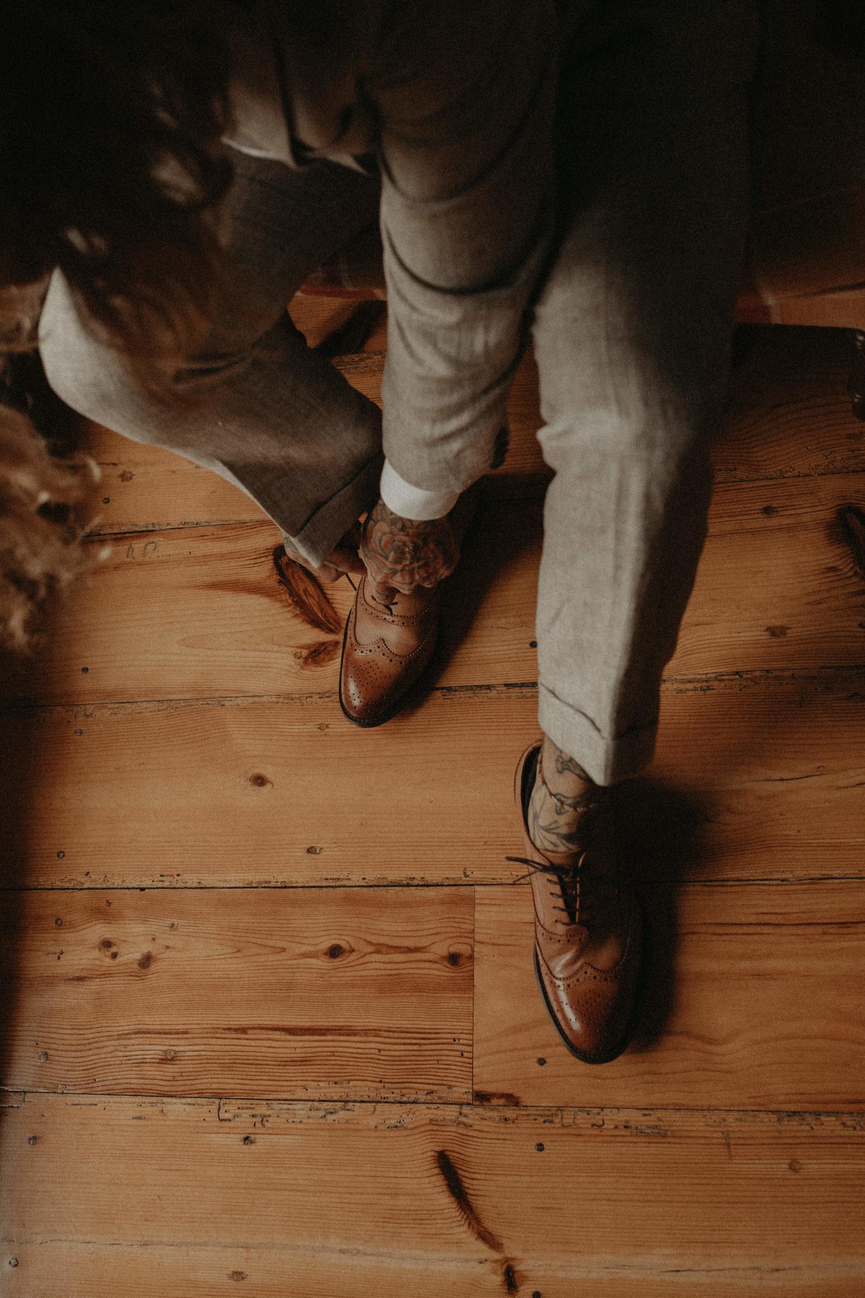 Novio vistiéndose los zapatos de boda