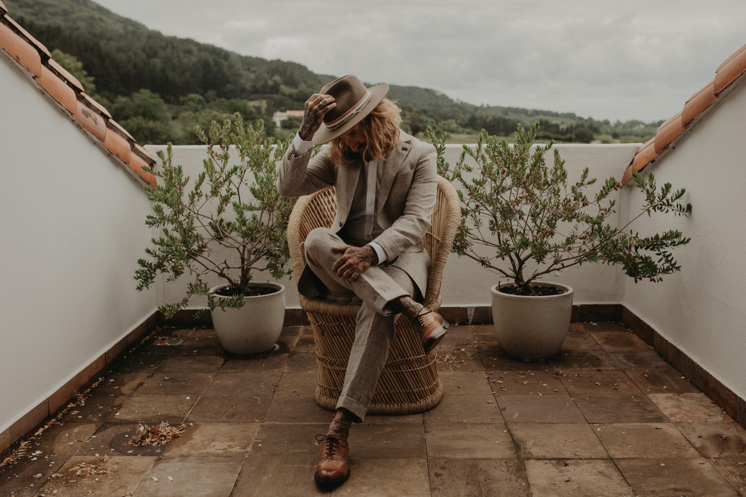 Novio posando con su traje y sombrero el día de su boda