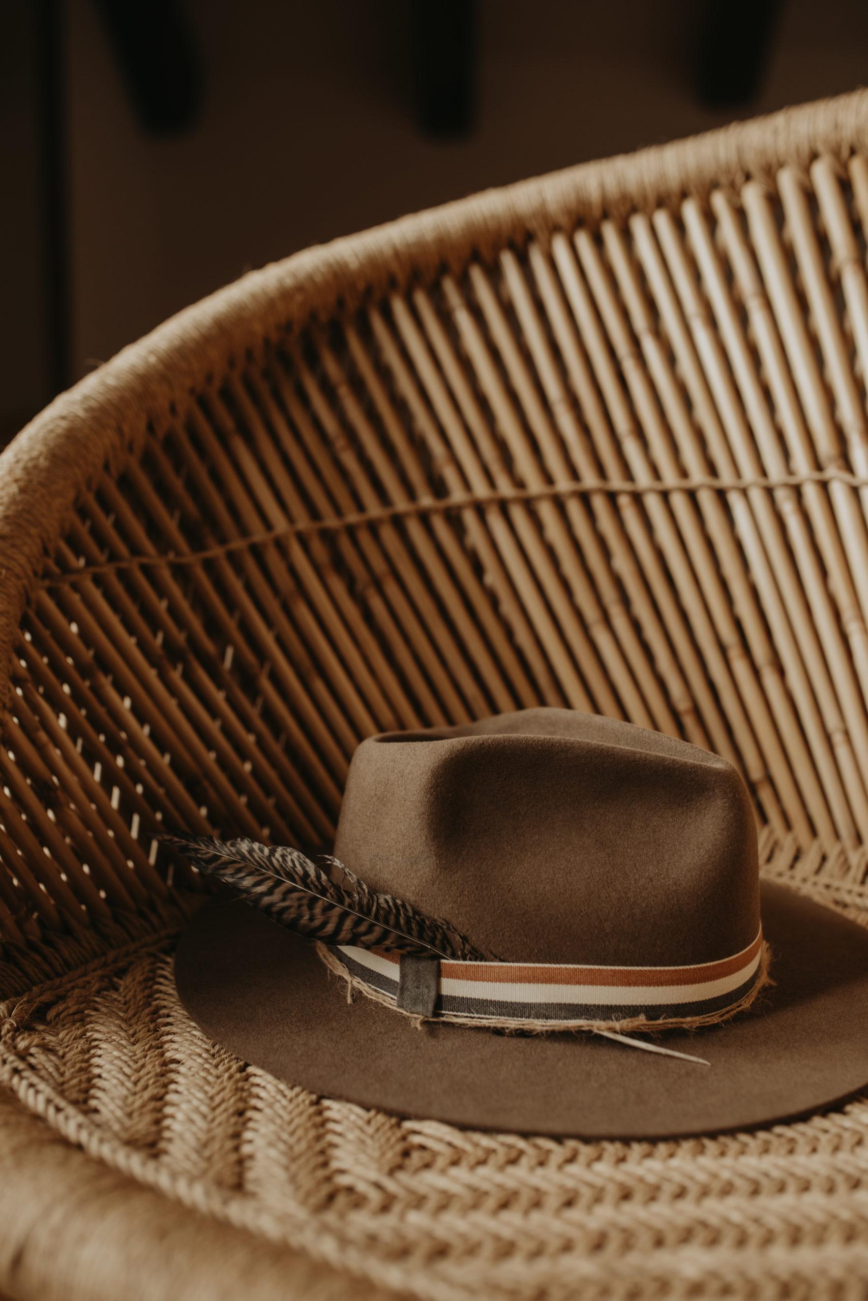 Sombrero de novio para boda sobre sillón de ratán