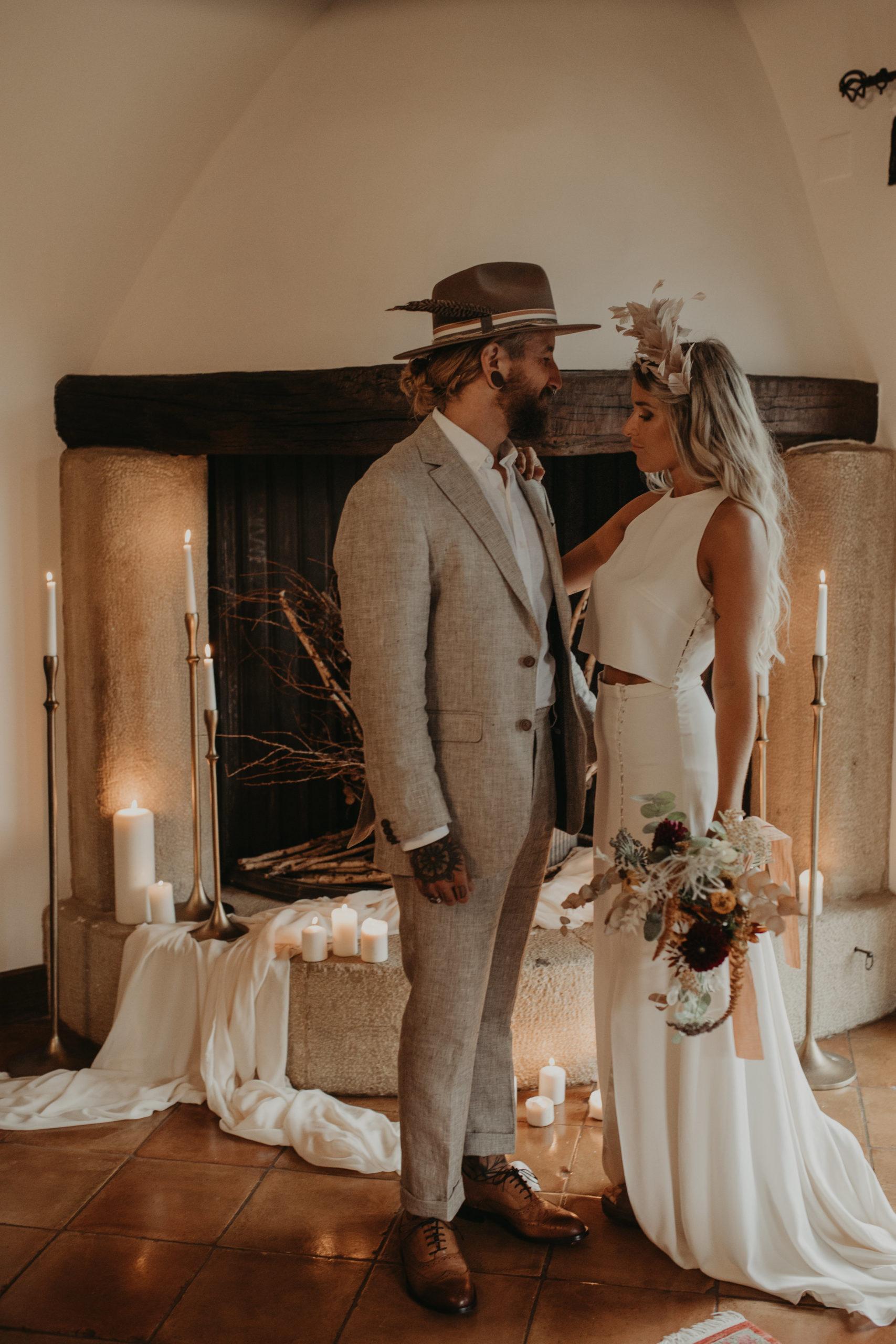 Posado de pareja de novios frente a una chimenea llena de candelabros