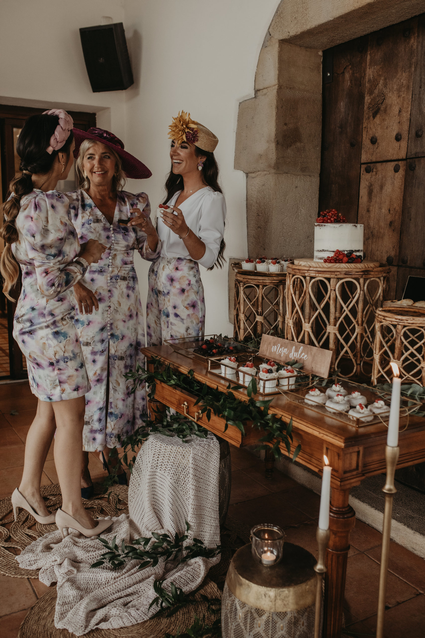 Invitadas de boda comiendo pasteles en un rincón dulce