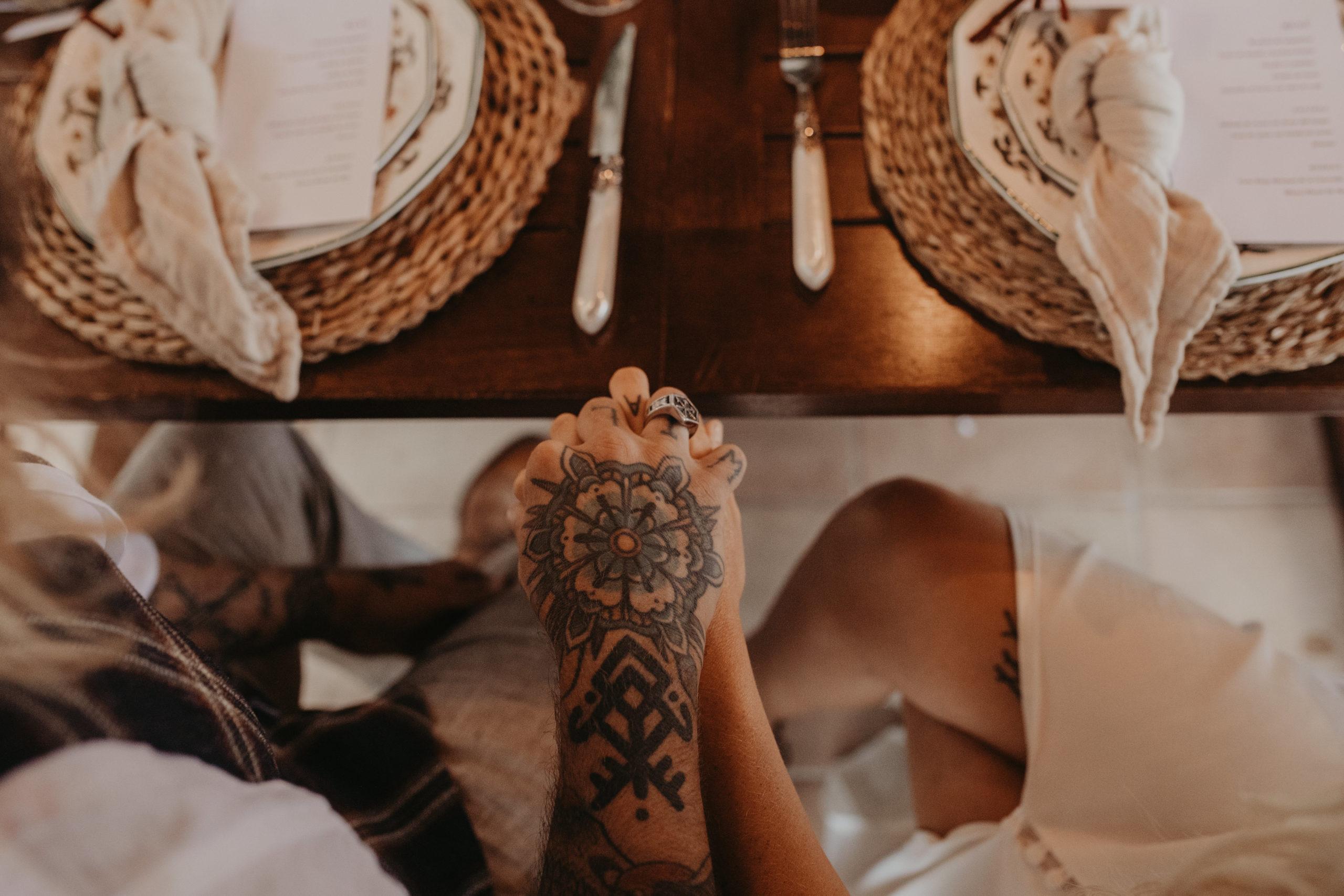 Novios tatuados cogiéndose de la mano