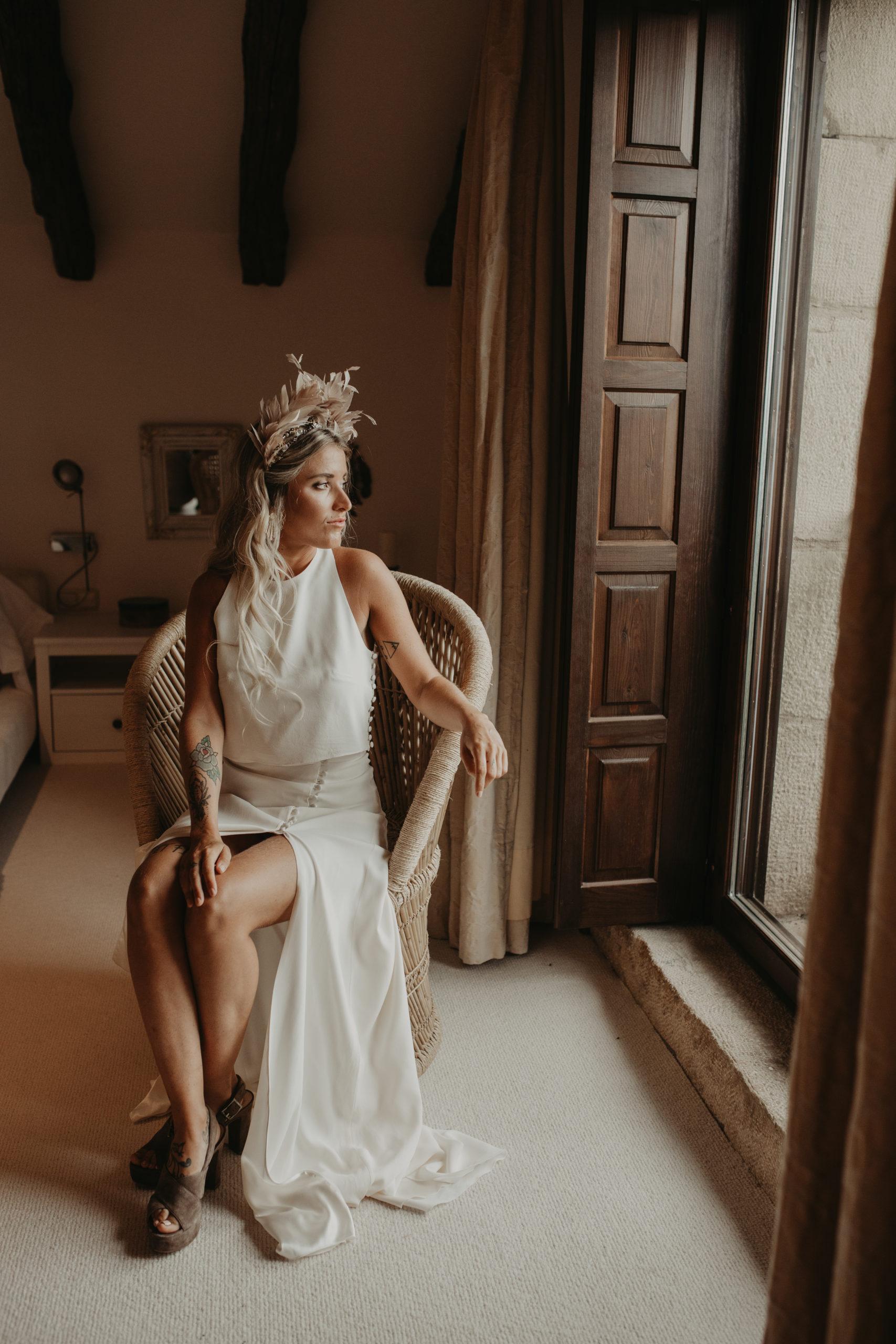 Novia posando con su vestido sobre un sillón de ratán