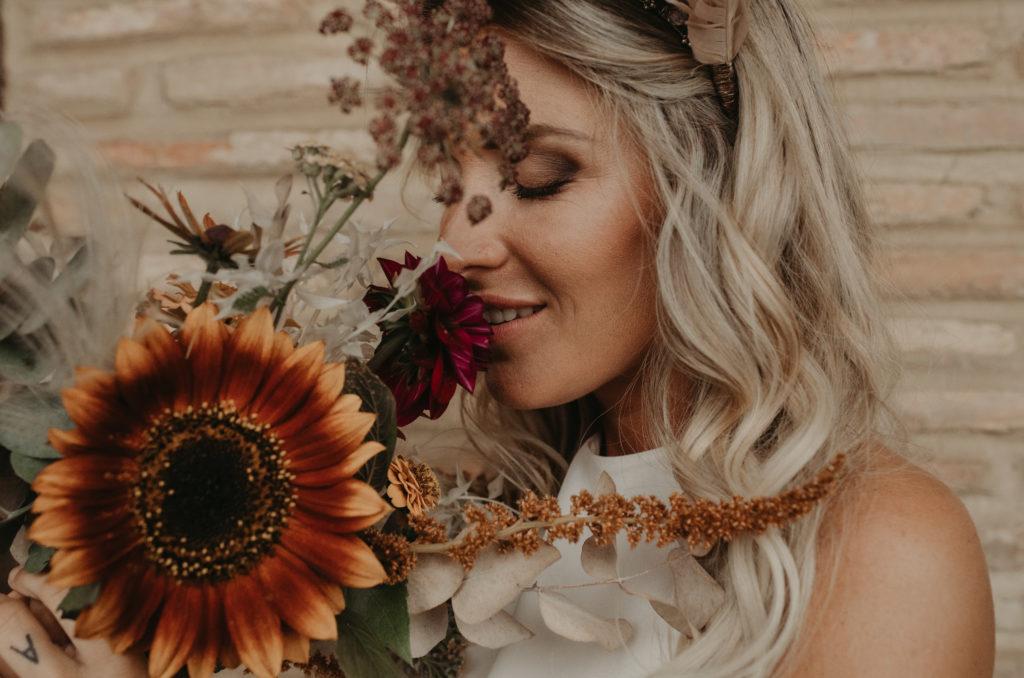 Novia oliendo su ramo de flores nupcial