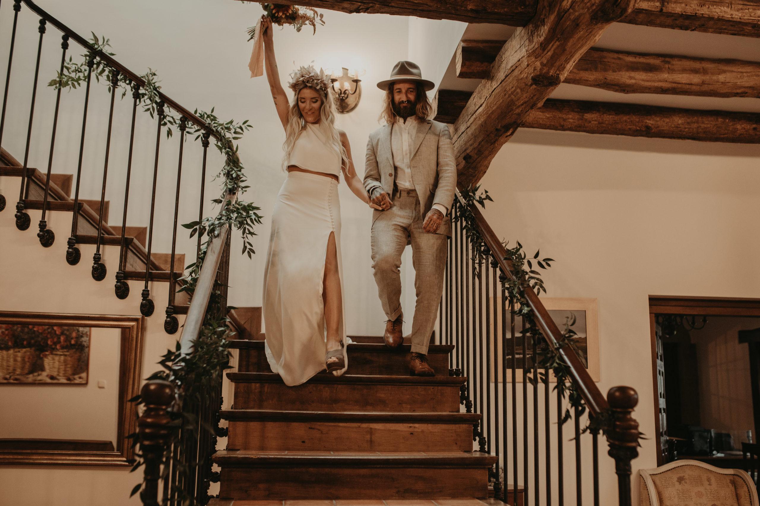 Pareja de novios bajando las escaleras a la ceremonia el día de su boda