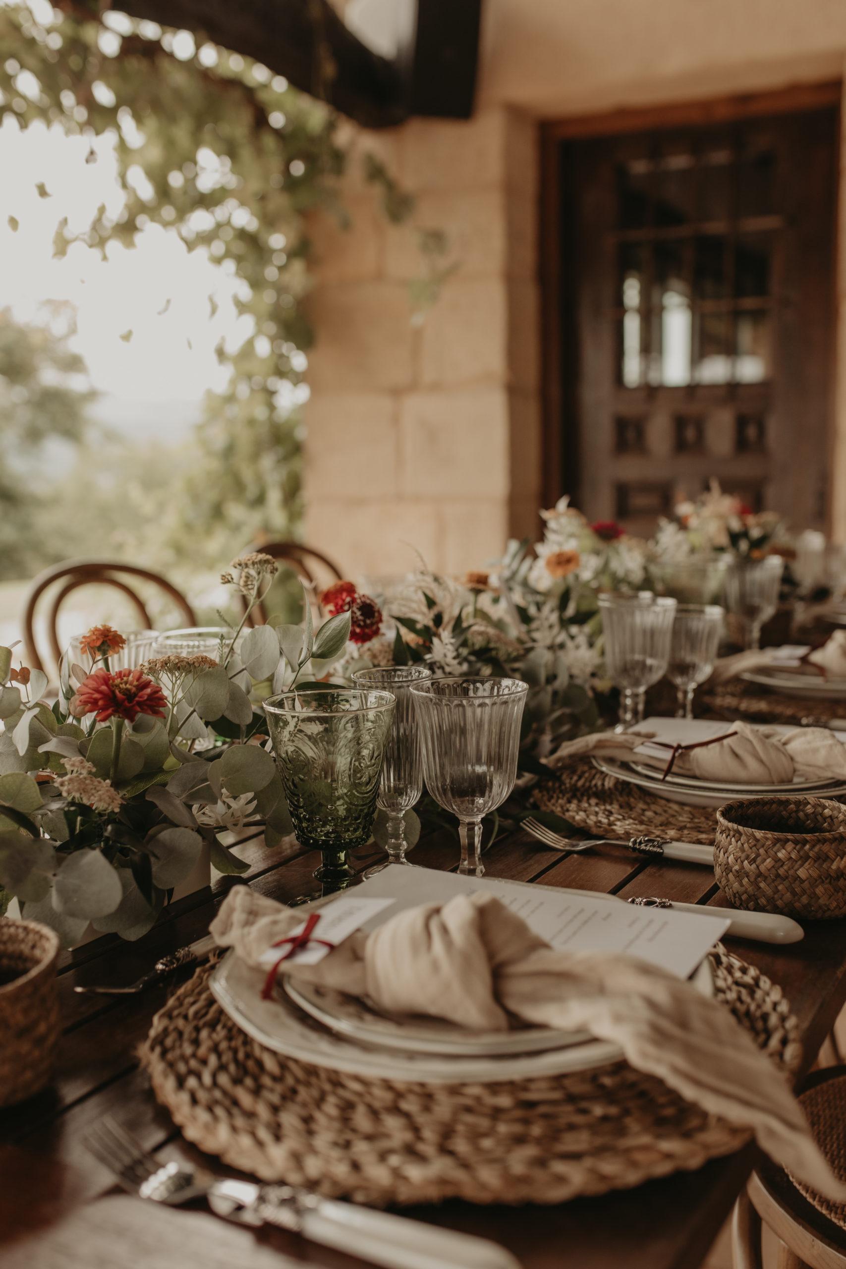 Bajoplatos, servilletas, copas, cubertería y decoración floral especial para un banquete nupcial