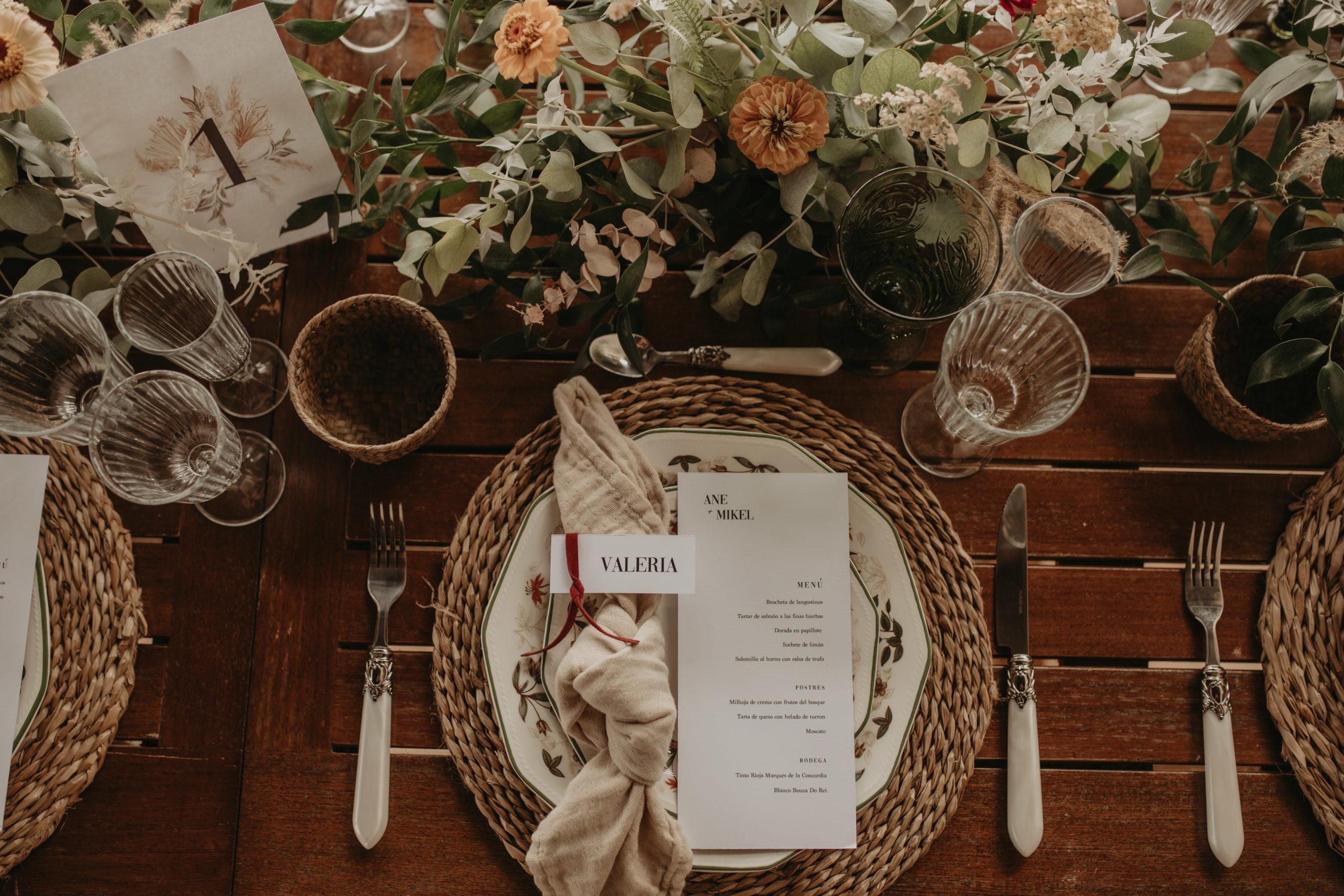 Bajoplato, vajilla, cubertería, copas y decoración floral en un banquete de boda