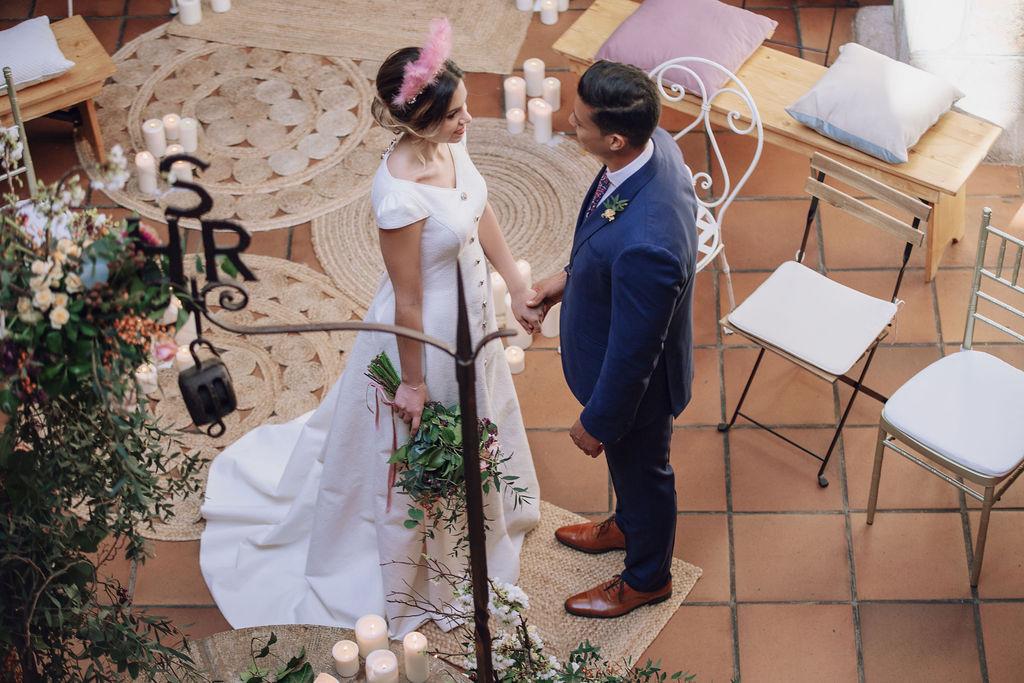Posado de novios en una ceremonia romántica con diferentes sillas y alfombras de yute