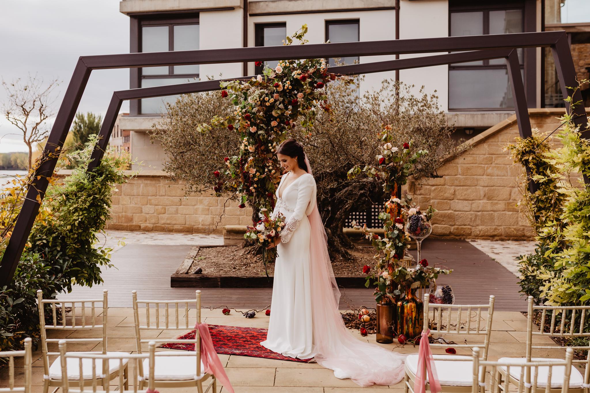 Novia posando en el altar con sillas tiffany doradas para los invitados
