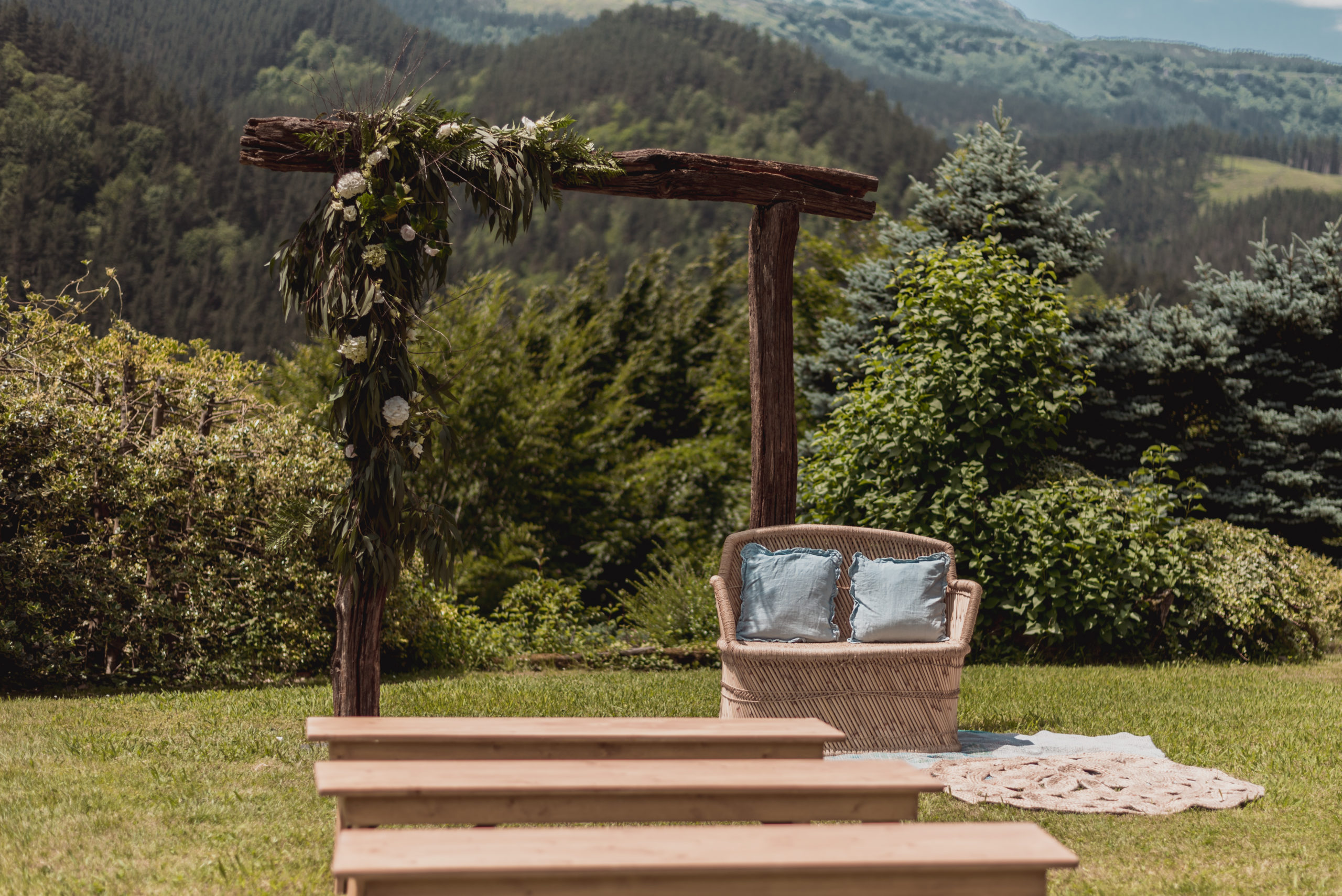 Ceremonia nupcial con bancos alargados de madera, sillón doble ratán con cojines y arco de madera natural