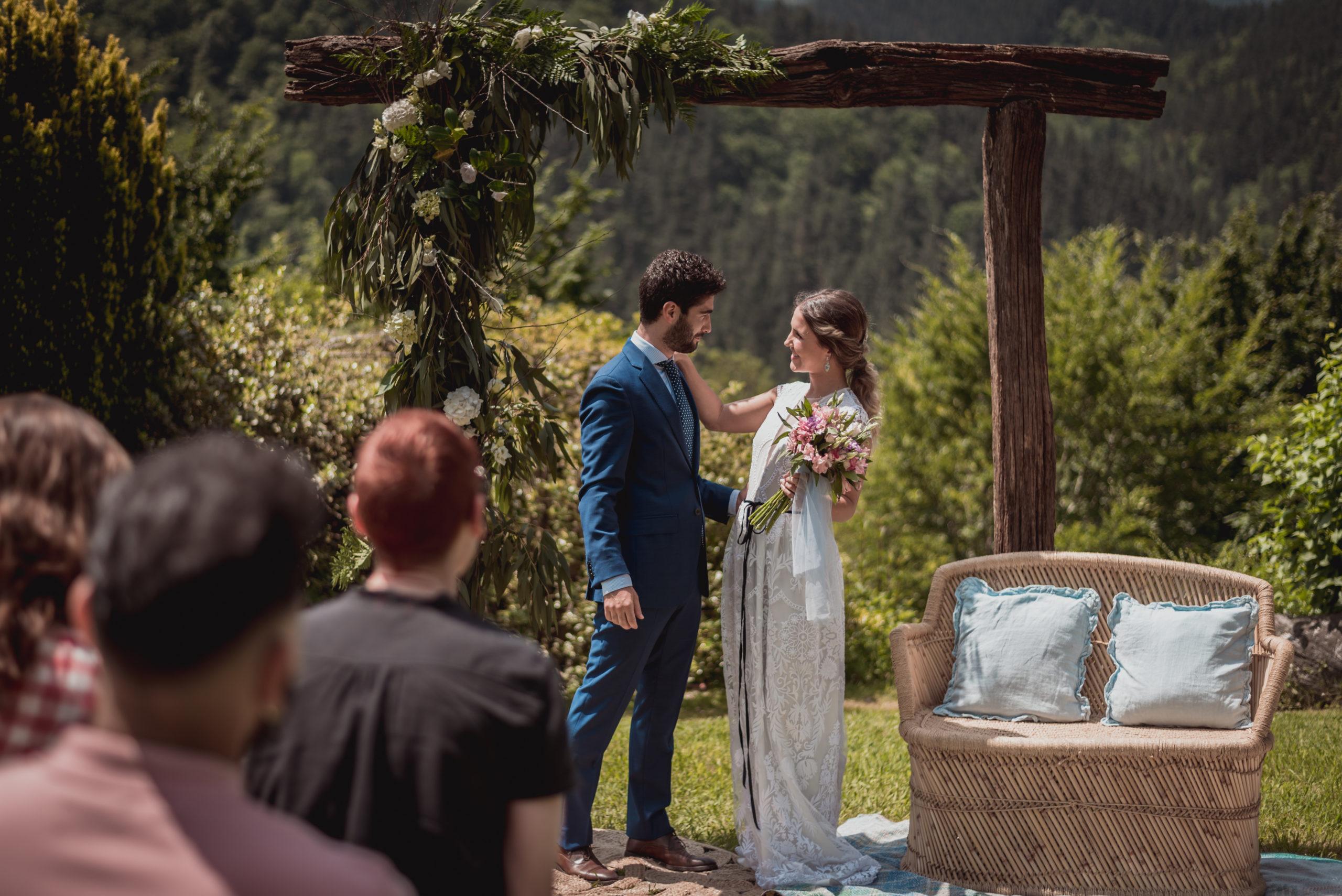 Novia y novio en su ceremonia de boda junto a un sillón doble ratán y un arco natural de fondo