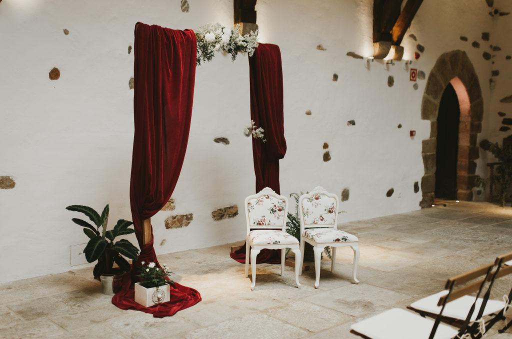 Arco con tela roja y sillas con estampado floral para la decoración de una ceremonia