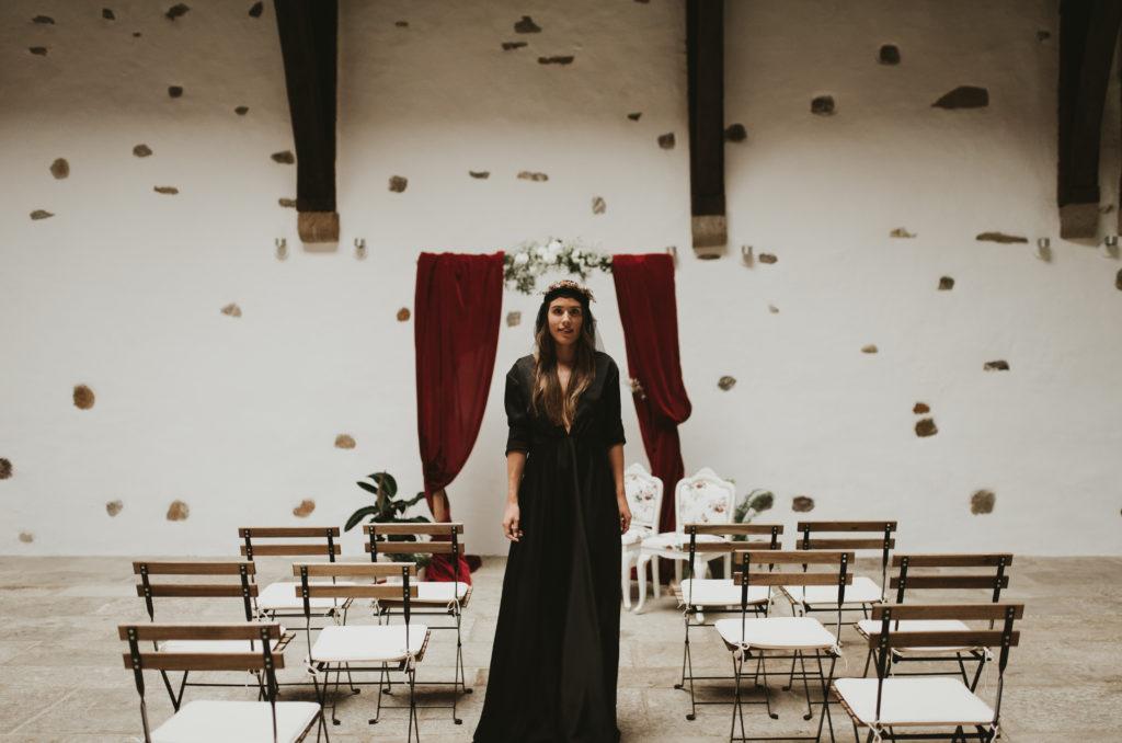 Novia con vestido negro, frente a arco rojo y con sillas de forja y madera al rededor