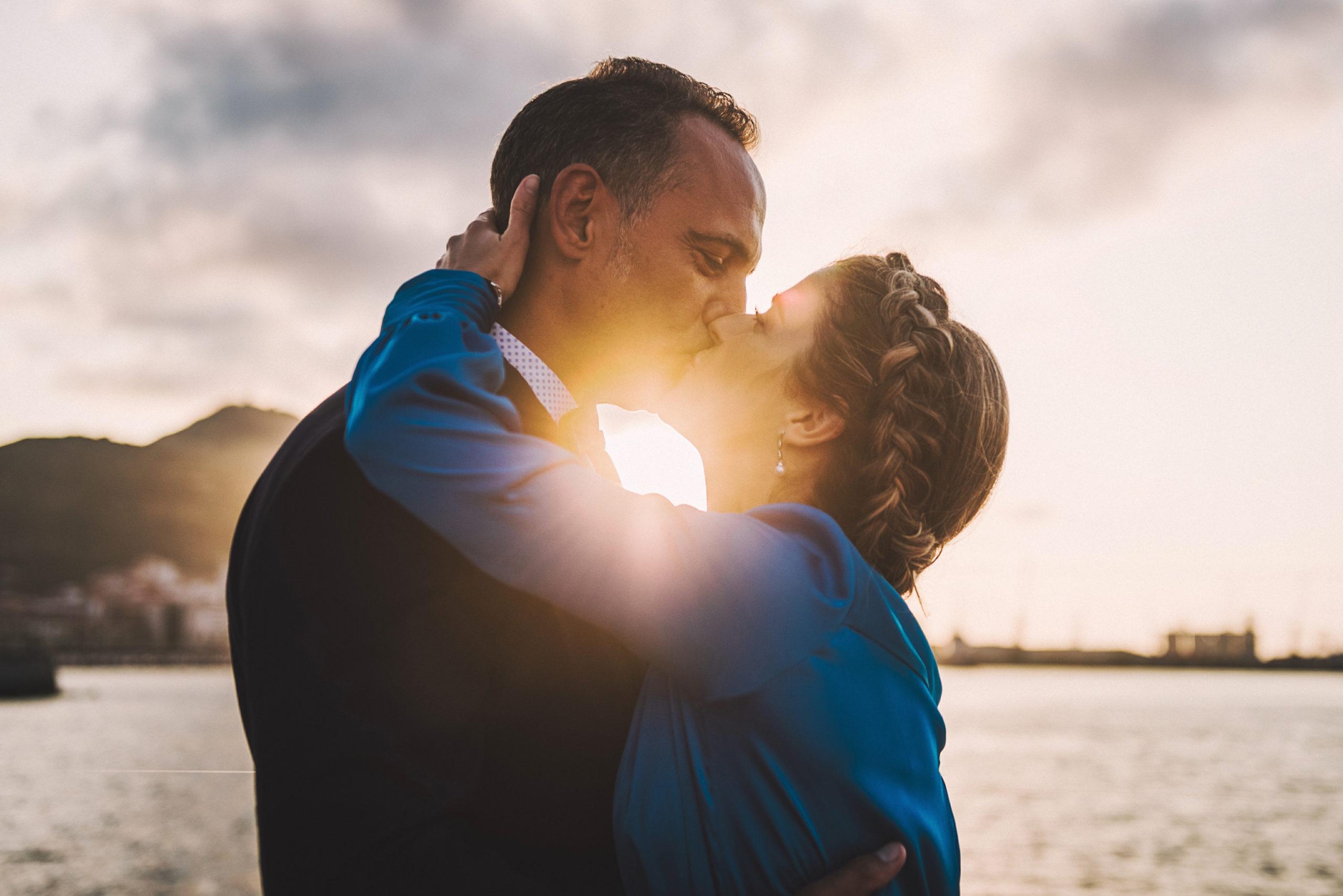 Beso de los novios al atardecer frente al mar