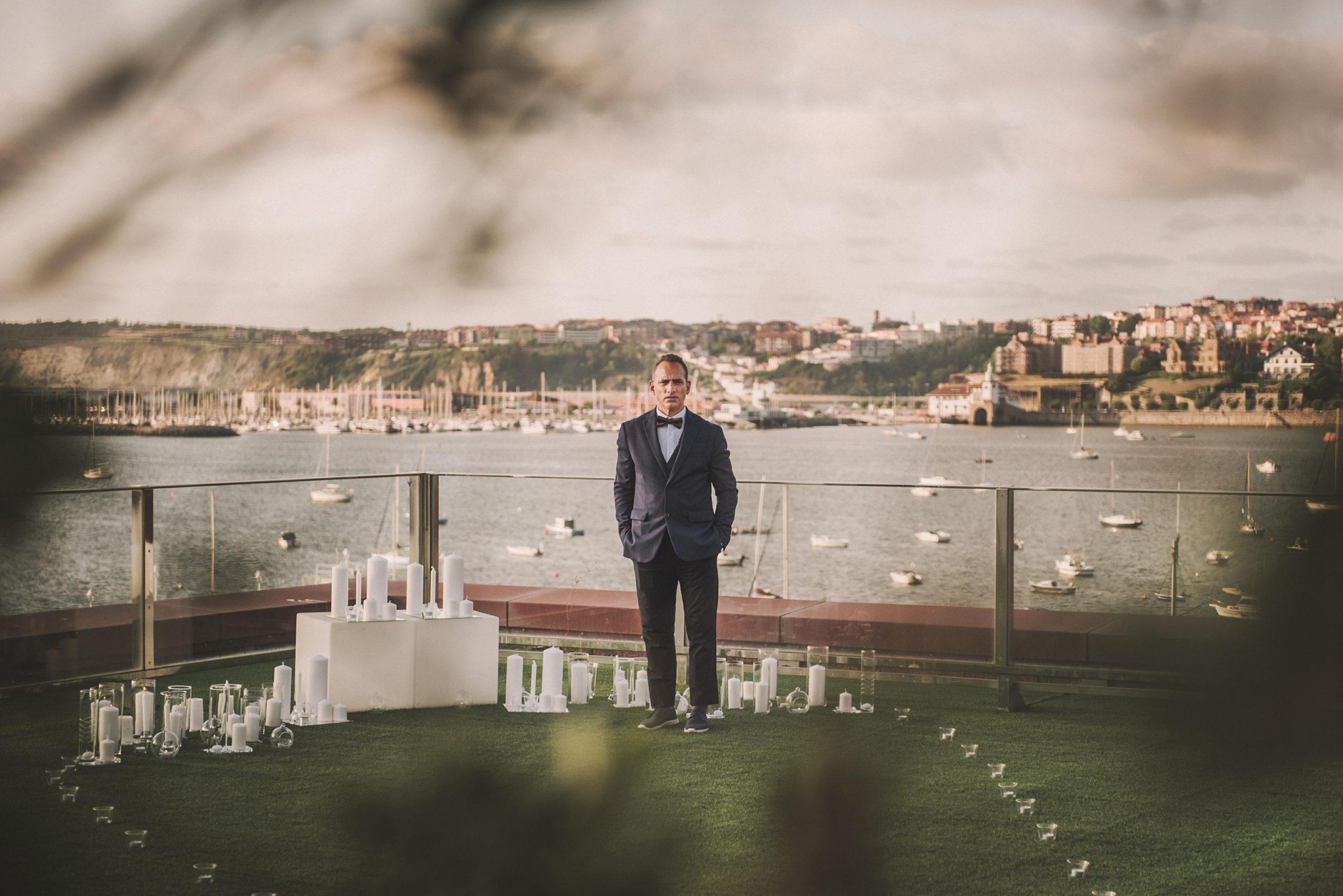 Novio a la espera de novia en un altar con velas frente al mar