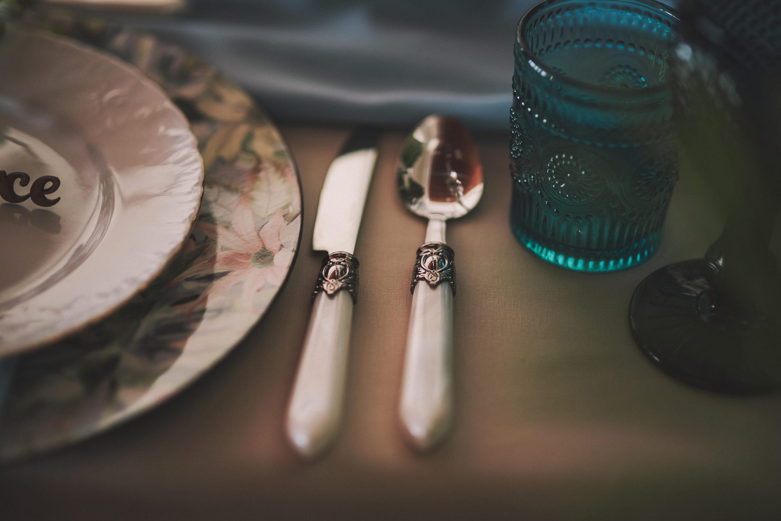 Cubiertos blancos, copas y vasos, cubiertos blancos y bajoplato floral
