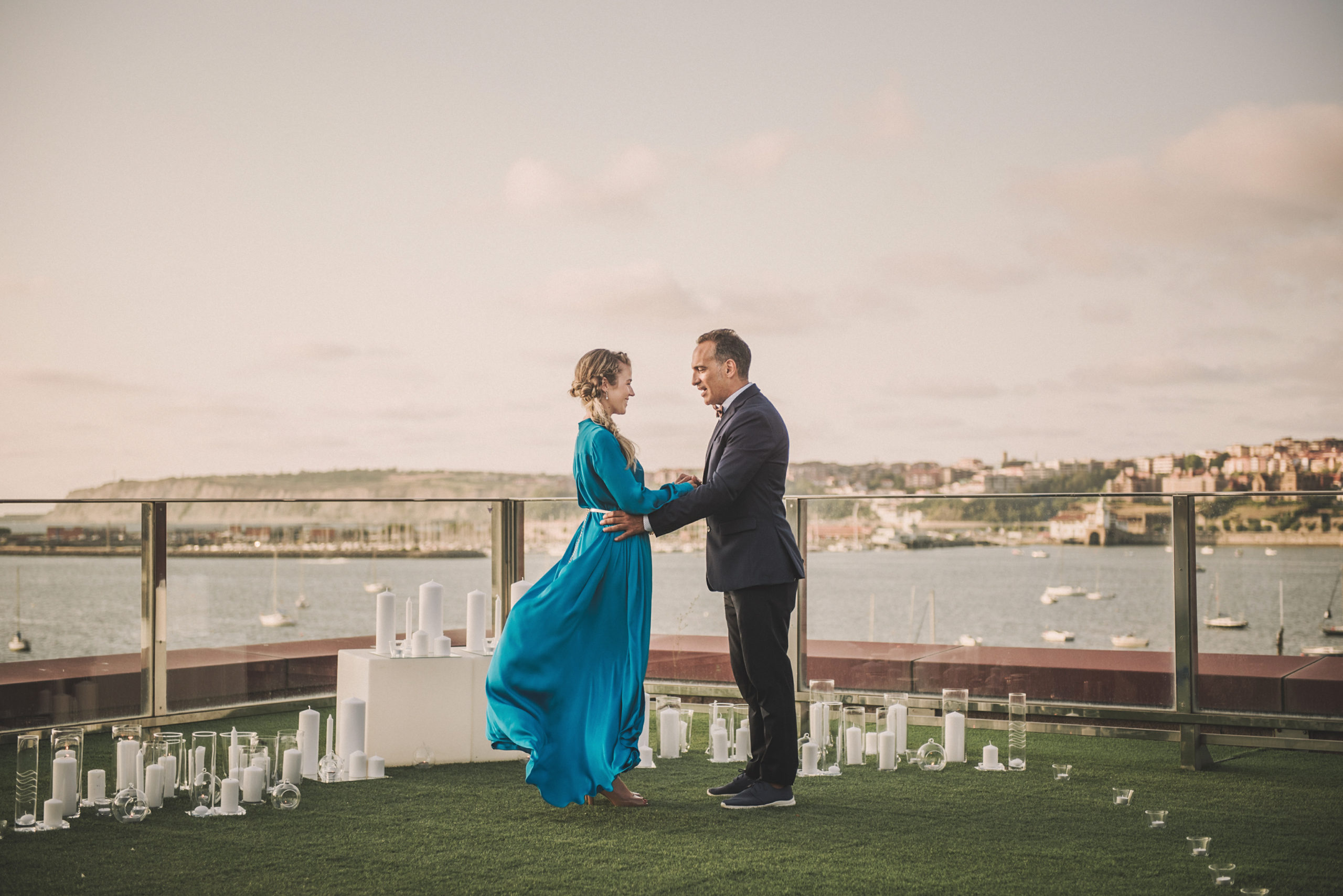 Momento pedida de mano novia vestida de azul y novio con traje frente al mar