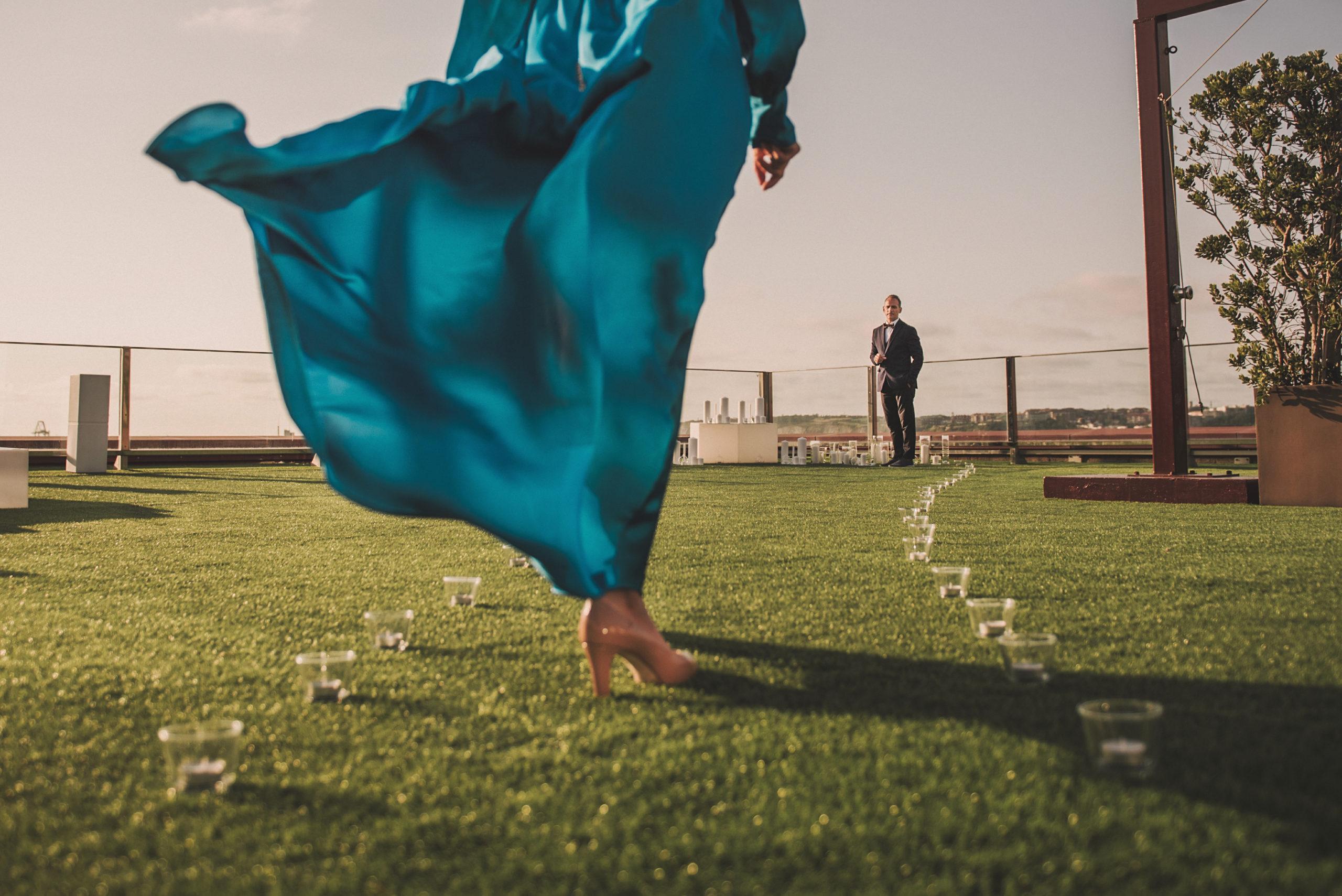 Vestido de novia azul pasando por pasillo de velas hasta llegar al novio