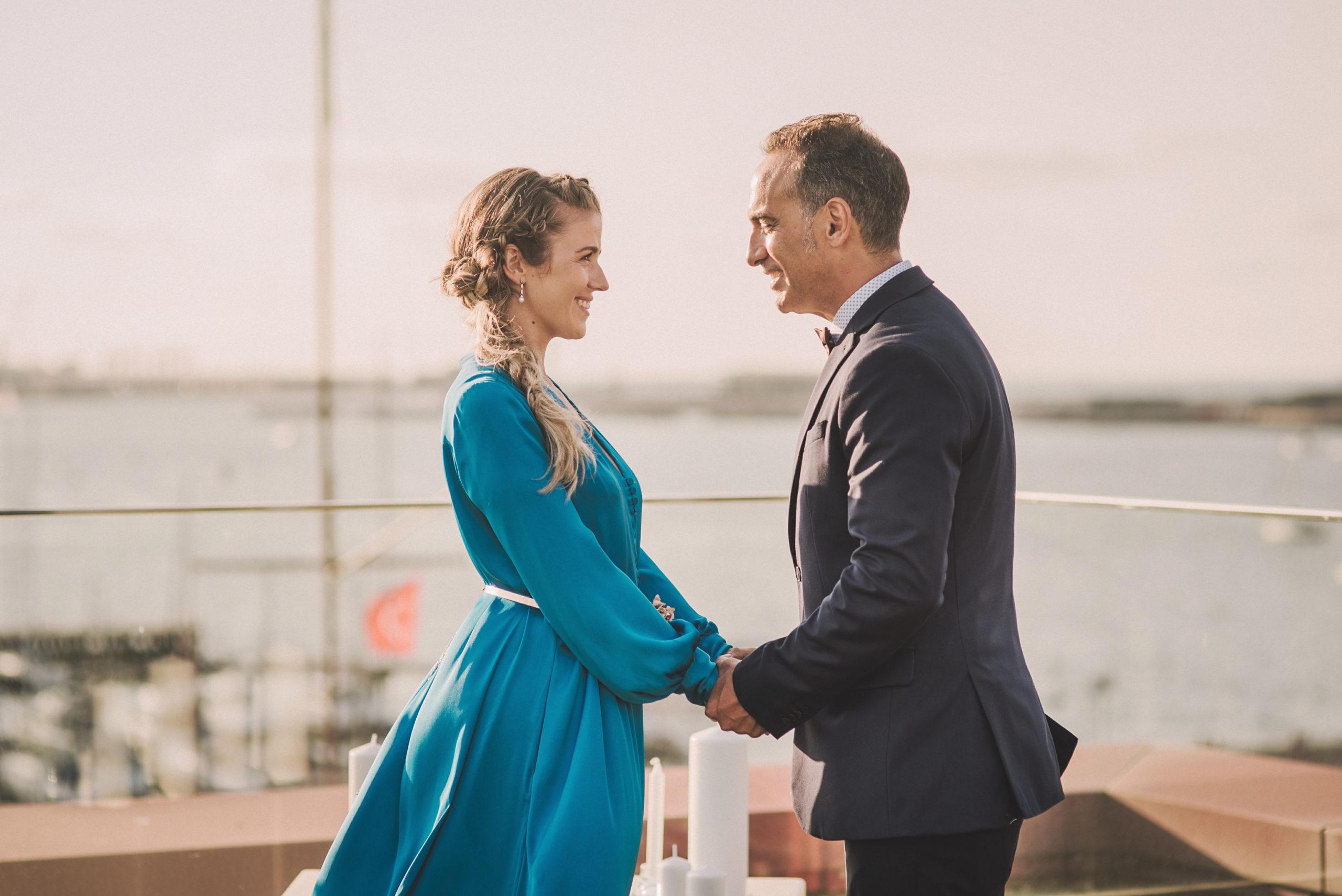 Novia y novio momento pedida de mano frente al mar