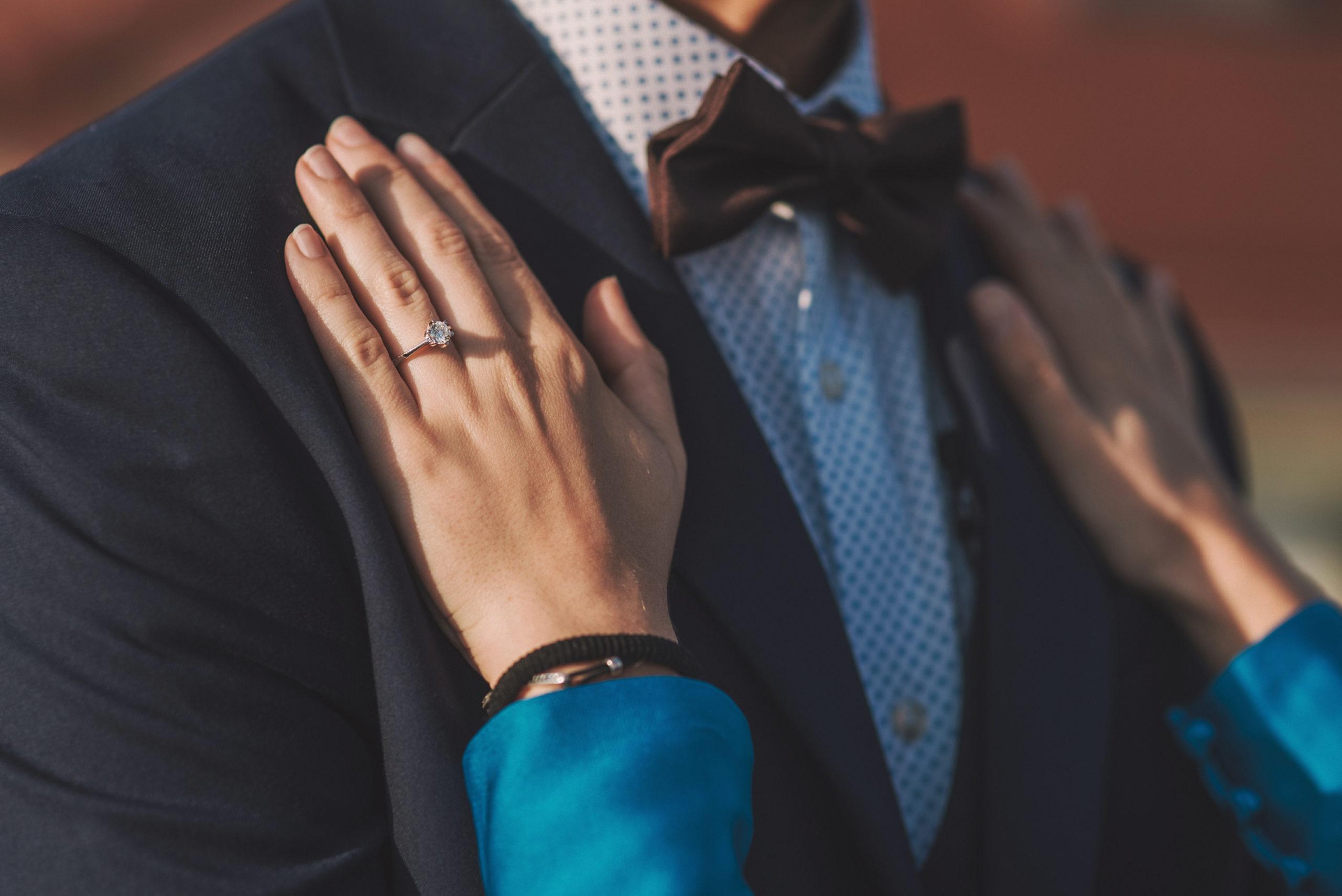 Novia apoya sus manos con el anillo de pedida en el novio