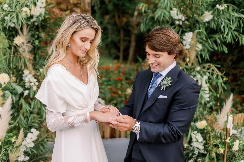 Novio pone a novia el anillo de compromiso el día de su boda