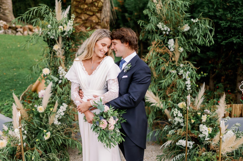 Novio agarra a novia con cariño por la espalda en el altar el día de su boda