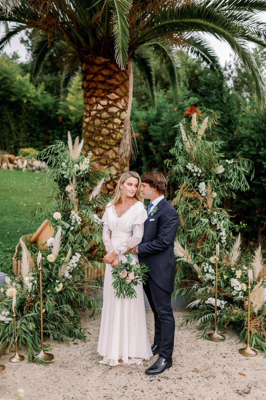 Novio con traje, novia con vestido y ramo de flores en el altar nupcial