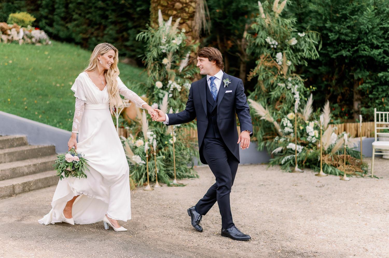 Novia y novio se agarran de la mano hacia el altar nupcial