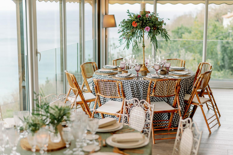 Decoración de mesa campestre en el mirador de ulia: sillas, mantel, bajoplatos, copas, cubiertos y centros de mesa