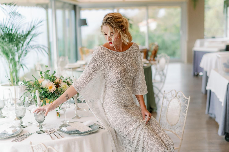 Novia sentada en la mesa con vestido de novia coge una copa gris en el Mirador de ulia