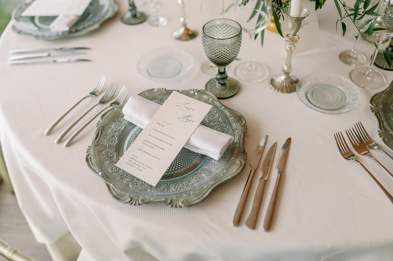 Mesa con bajoplatos, cubertería, copas, candelabros y platos de pan y minutas