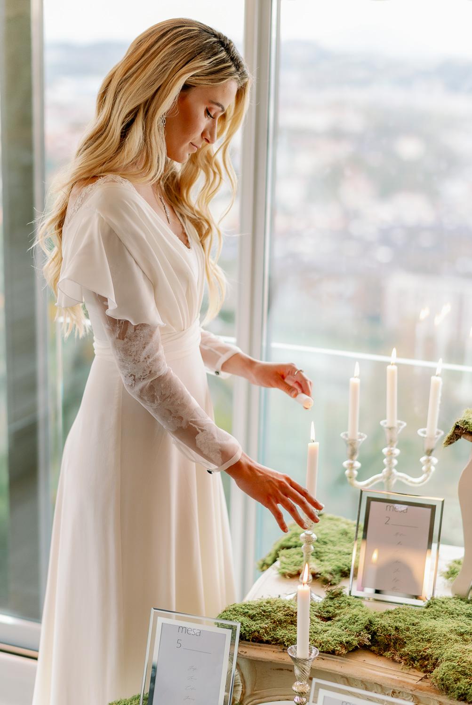 Novia en el seating plan encendiendo velas de los candelabros