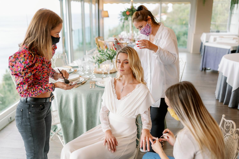 Maquiladoras maquillando y peinando a la novia el día de su boda