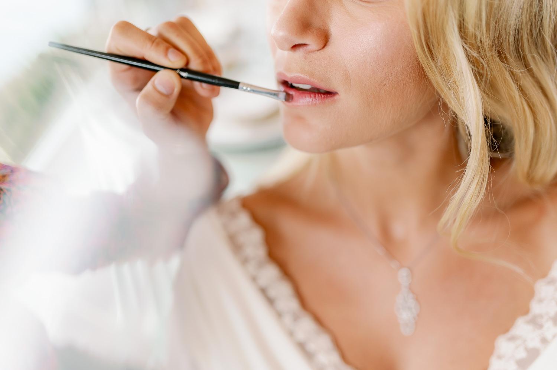 Maquilladora pinta los labios a la novia