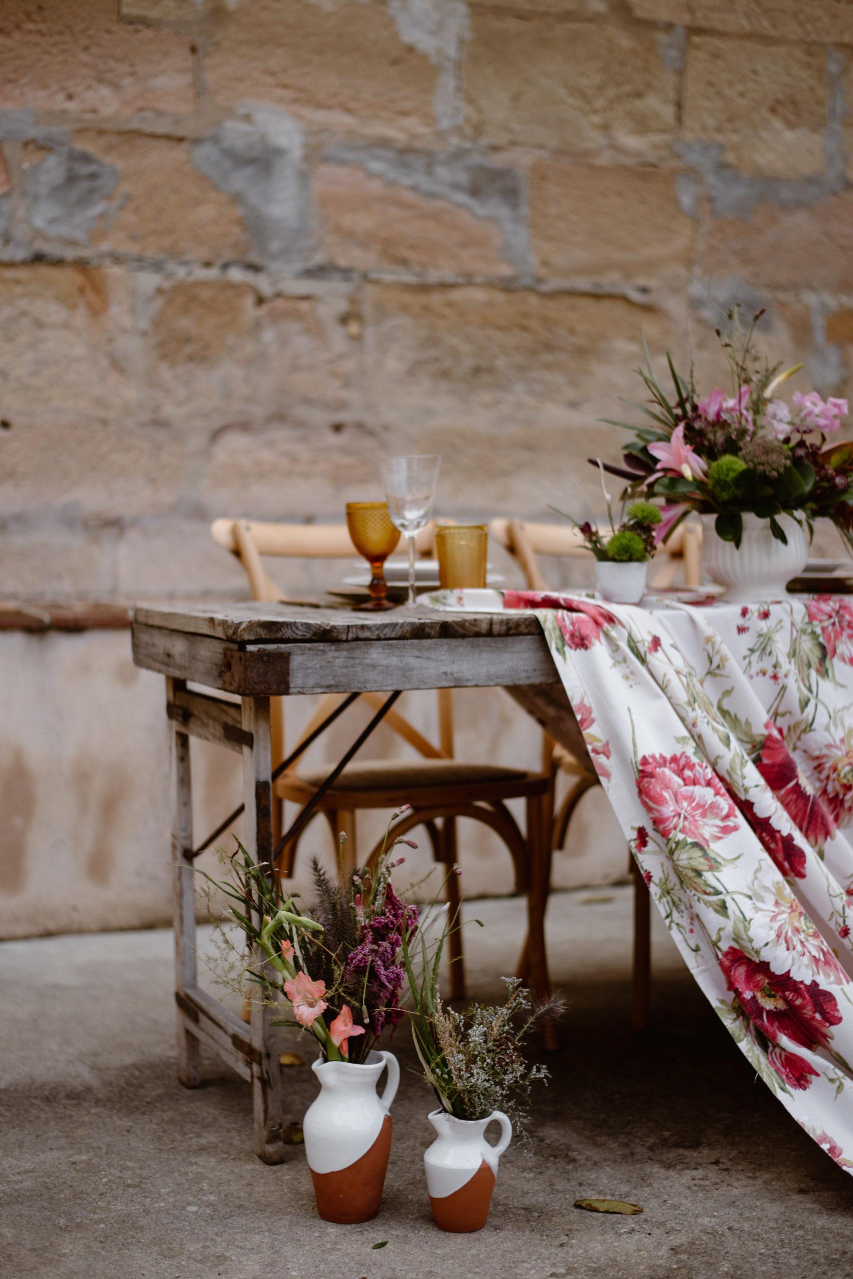 Mesa rústica con mantel floral, vasijas, sillas de madera y copas de colores en alquiler