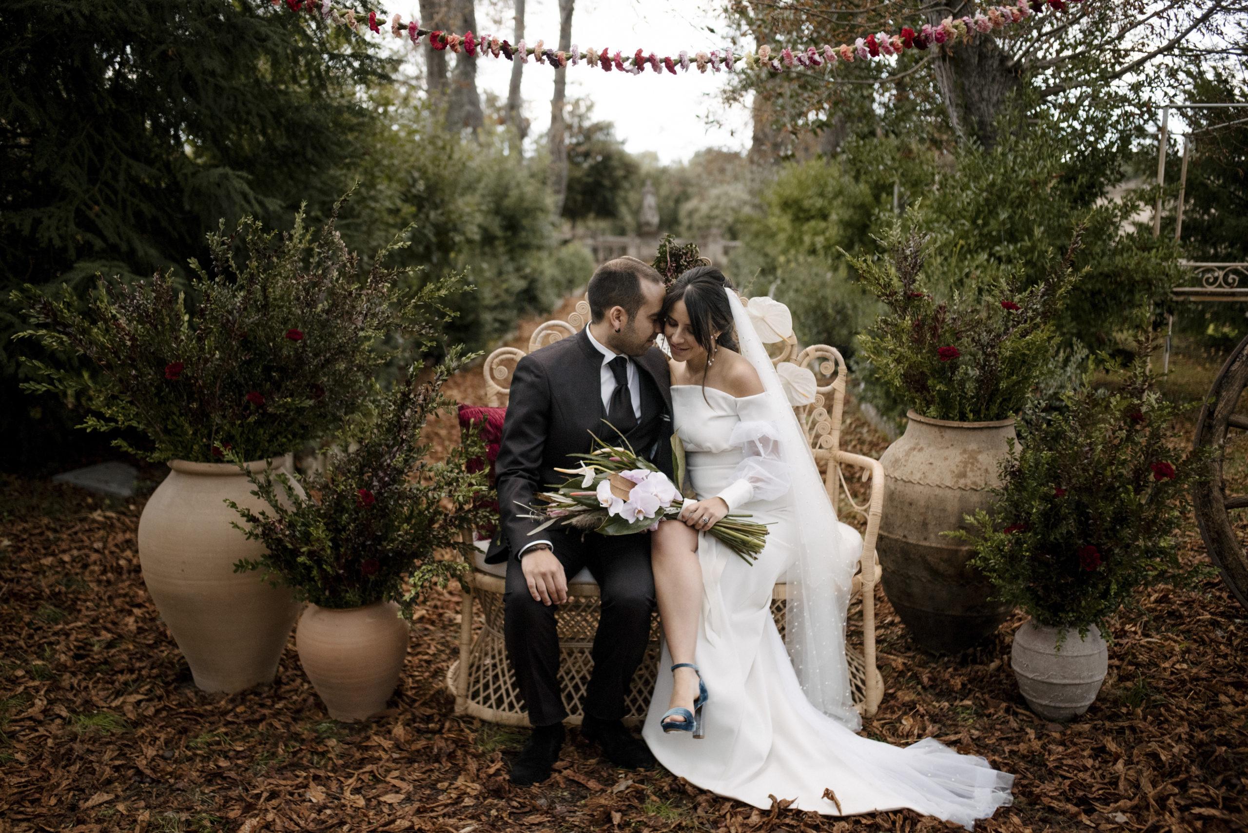 Novia y novio sentados en el sillón ratán pavo real en la ceremonia de boda