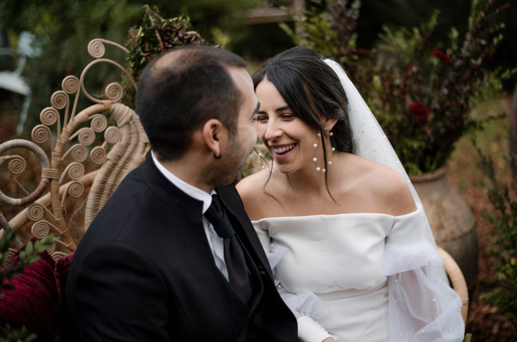 Novia y novio sentados en el sillón ratán pavo real en la ceremonia nupcial