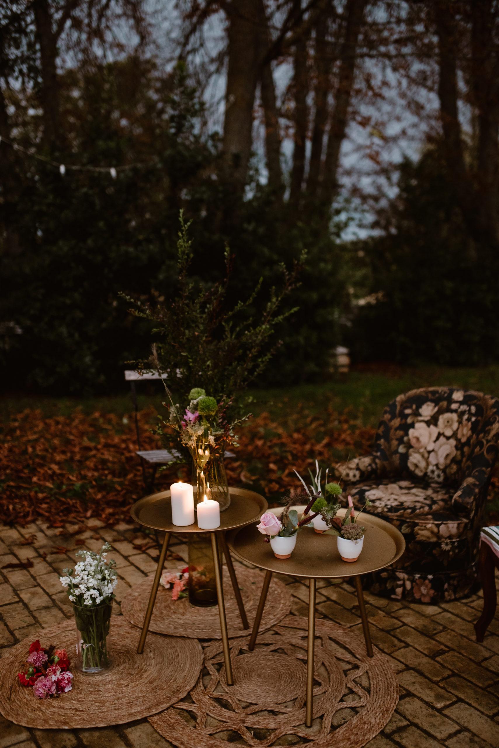 Mesa auxiliar dorada con alfombras redondas de yute y sillones de estampados florales en alquiler