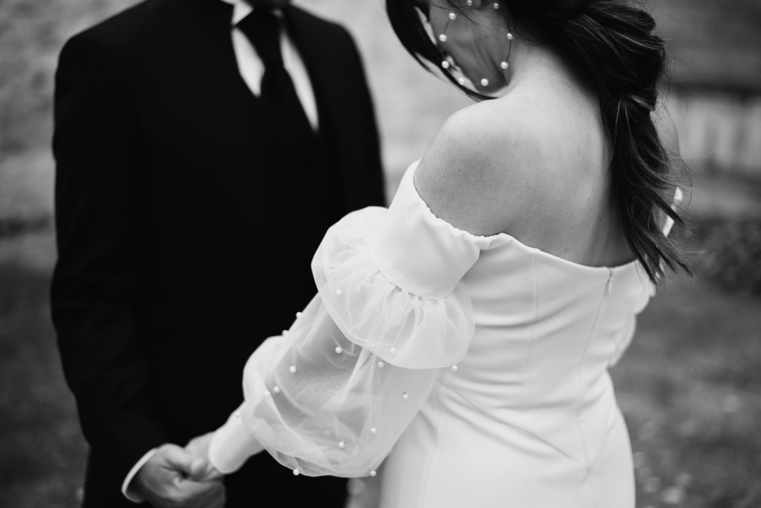 Novio con traje y novia con vestido agarrándose de la mano