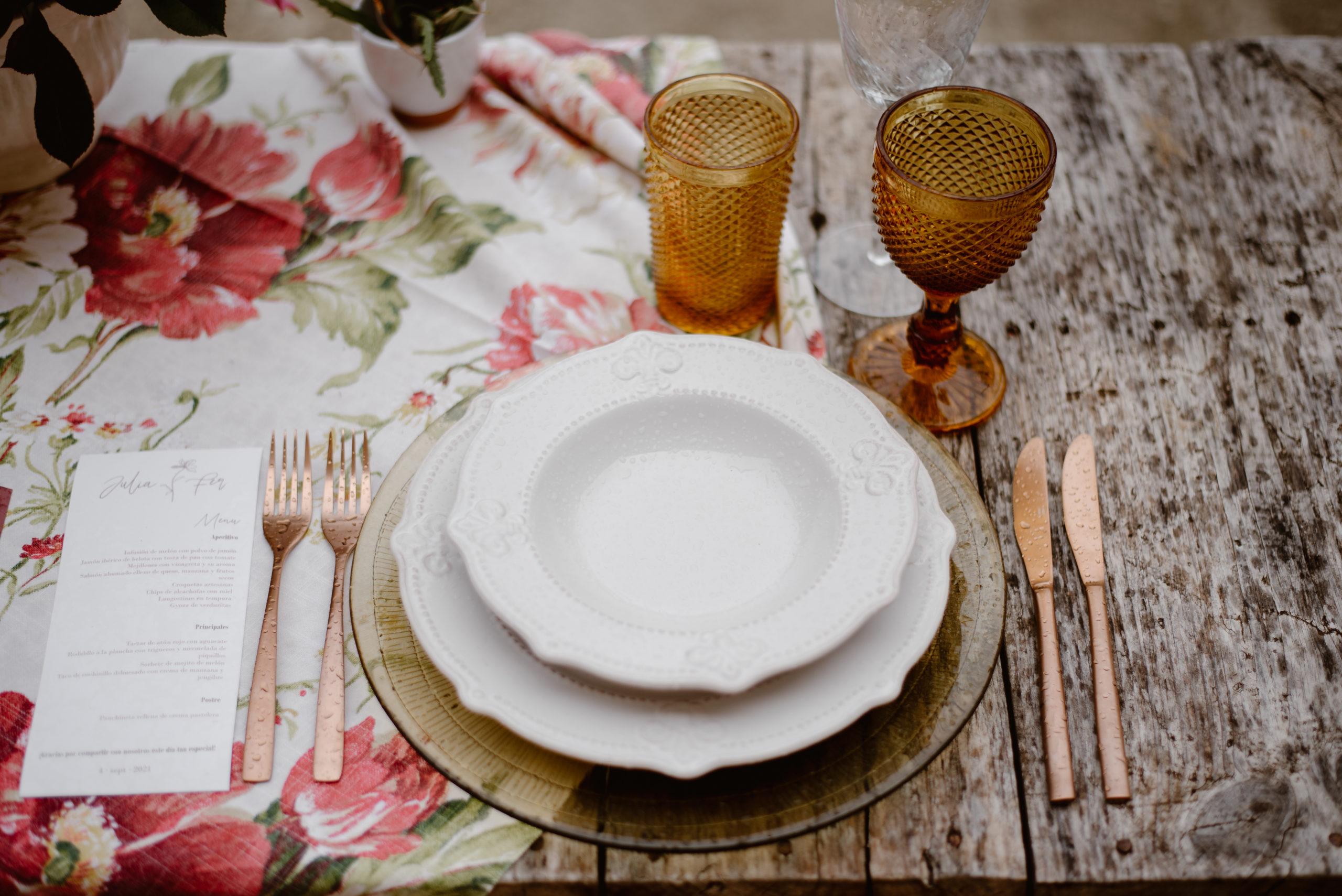 Bajoplato, platos, cubiertos, copas de colores, mantel floral y minutas personalizadas