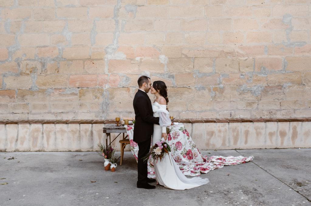 Mesa rústica con mantel floral  moderno en la boda detrás de  pareja de novios